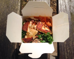 Takeaway carton filled with salad and halloumi.