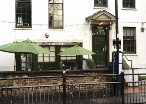 White cafe facade with green-trimmed windows and door. Two parasols outside.