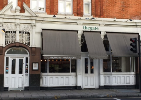 White restaurant facade with black awnings, large windows and two doors.