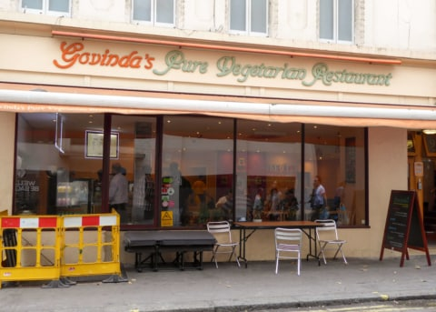 Beige restaurant facade with orange awning, large windows. Tables and chairs outside.
