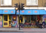Painted cafe facade with blue awning, large windows and door. Customers sitting outside.