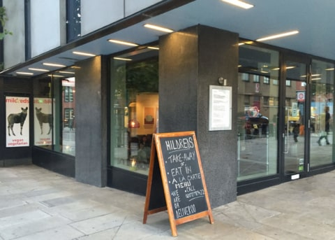 Black restaurant facade with glass door and windows. Sandwich board outside.
