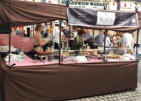 Brown and pink market stall with servers and onlookers.