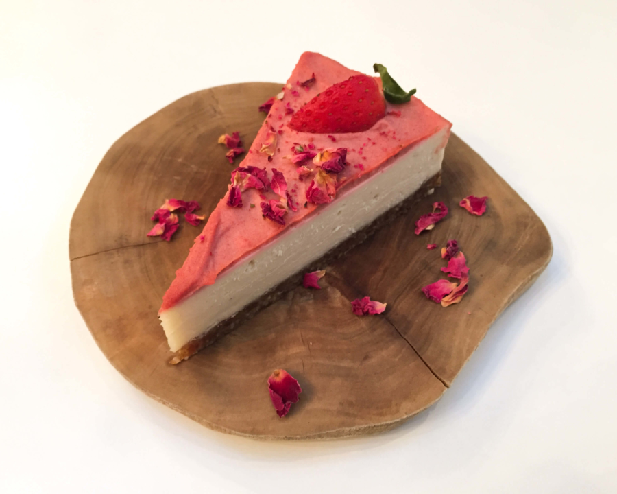 Piece of strawberry cheesecake with flower petals.