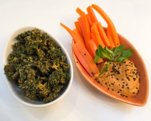 Kale chips alongside carrots with hummus dip.