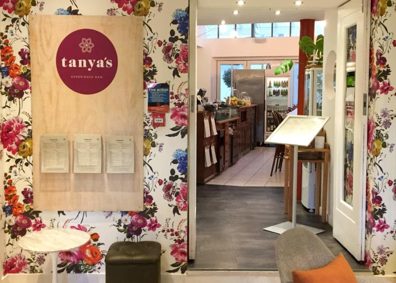 Indoor floral painted cafe facade with open door.