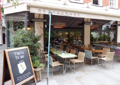Beige restaurant facade with large windows. Table, chairs and sandwich board outside.