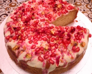 Pistachio cake topped with pomegranate and rose petals.