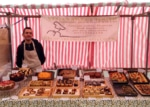 Red-striped market stall with rows of baked goods, server inside.