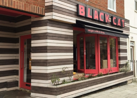 Brown and white restaurant facade with red-trimmed bay window and door.