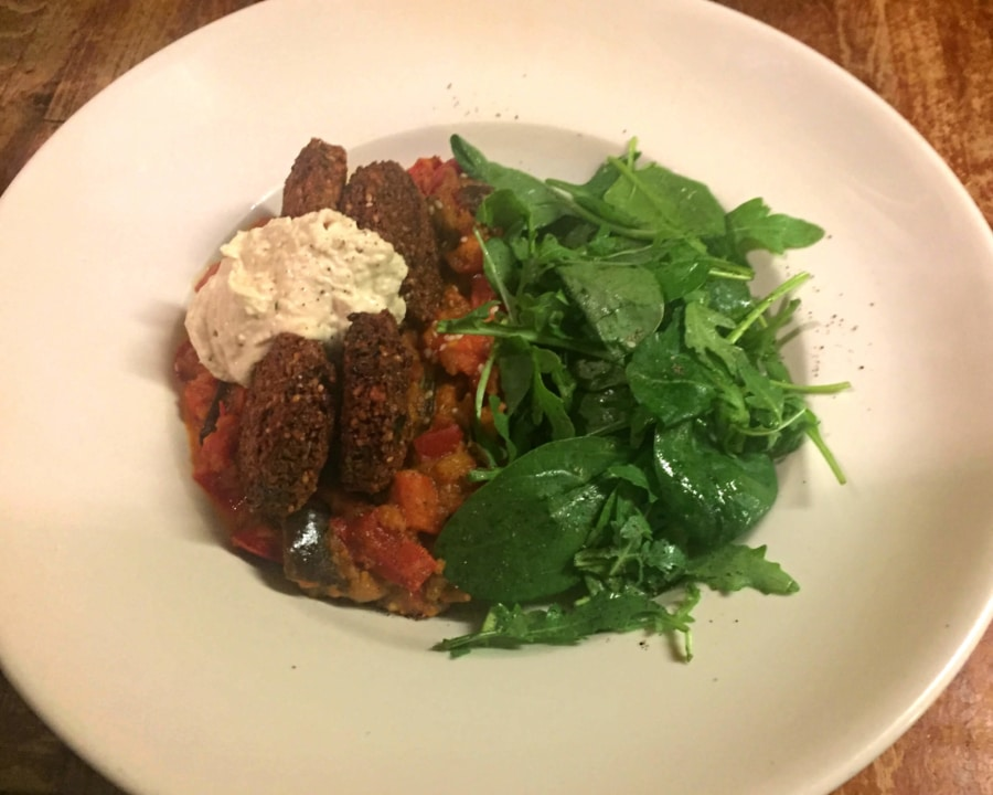 Falafel, aubergine and red pepper harissa casserole with salad.