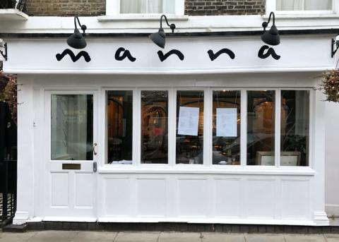 White restaurant facade with windows and door.