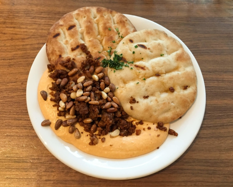 Hummus with pine nuts and two pieces of flat bread.