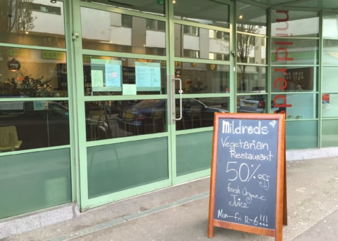 Green restaurant facade with glass door and windows. Sandwich board outside.