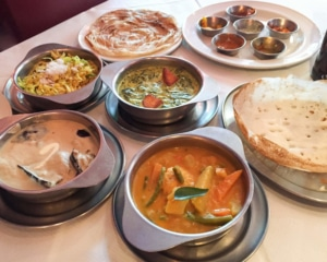 Assorted dishes of curries, sides, rice and paratha bread.