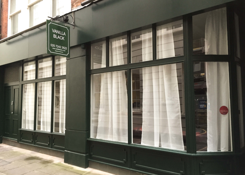 Green restaurant facade with white curtained windows.