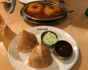 Two samosas with dips. Two lentil donuts in soup.